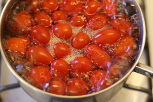 cherry tomatoes boiling in a pot of water