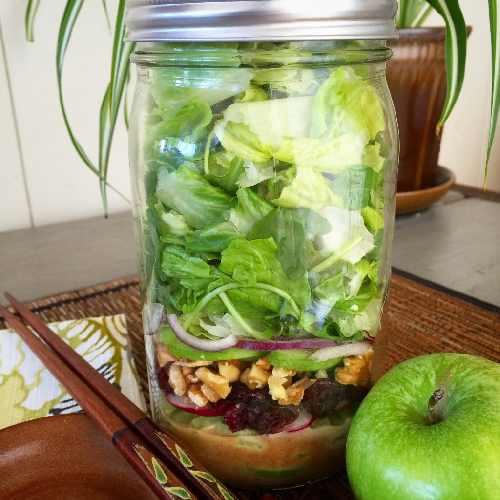 Canning jar filled with layers of dressing, fruit, nuts and vegetables making up a Waldorf Salad