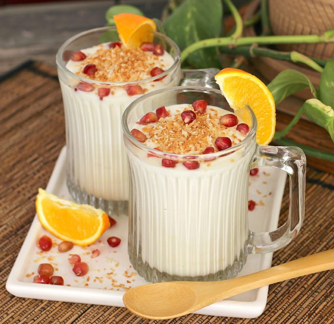 White chocolate coconut mousse topped with toasted coconut and pomegranate seeds in clear glass cups with an orange wedge