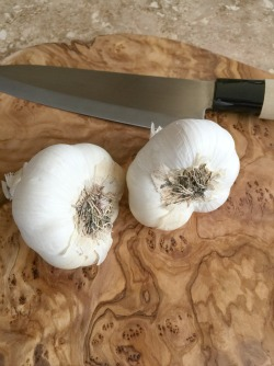 2 bulbs of garlic on a cutting board with a knife