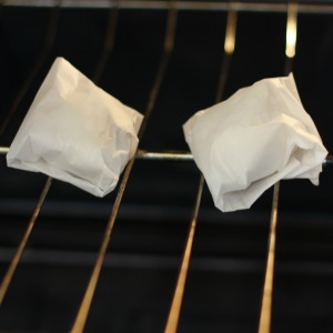 2 individually wrapped garlic cloves in parchment paper on an oven rack