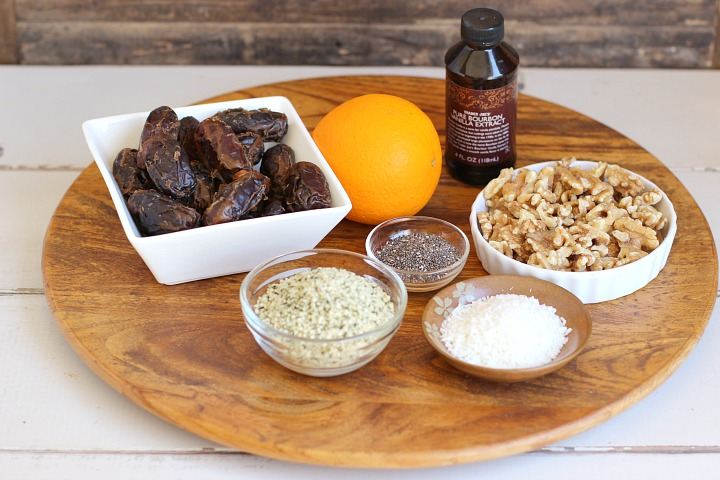 Wooden surface with a bowl of dates, walnuts, hemp hearts, chia seeds, coconut, an orange and a bottle of vanilla extract.