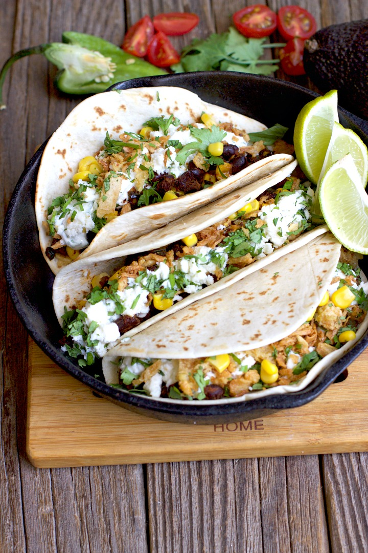 Black Bean & Corn soft tacos in a cast iron pan on a wooden surface.