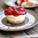 Mini cheesecake cupcake on a brown plate with a strawberry topping