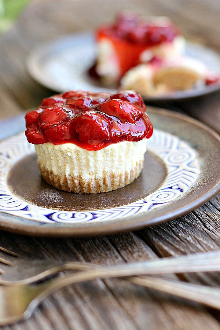 Mini Cheesecake Cupcake with strawberry topping on a brown plate.