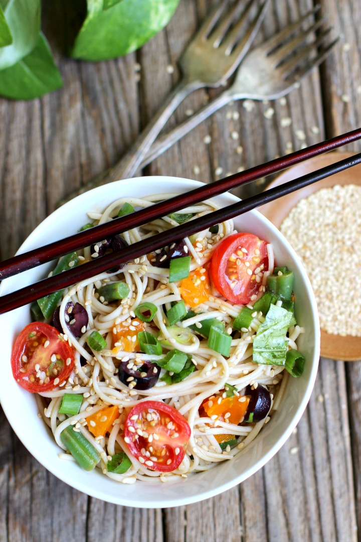 Soba noodles mixed with cherry tomatoes, green onions, kalamata olives, green beans and sesame seeds in a white bowl with chopsticks on top