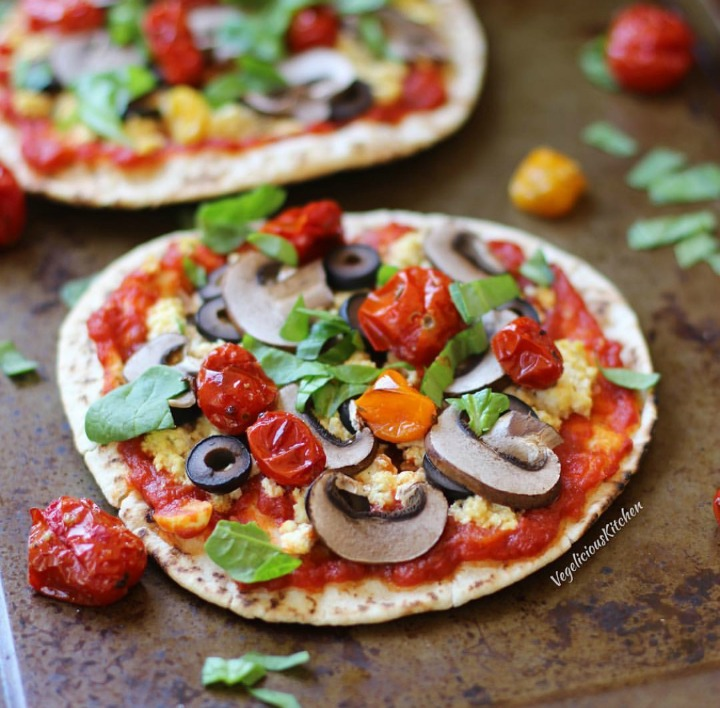 Pita pizza topped with tofu ricotta, tomato sauce, mushrooms, black olives, roasted tomatoes and fresh basil