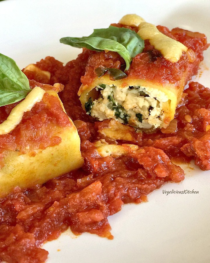 Manicotti stuffed with tofu ricotta and topped with tomato sauce and fresh basil