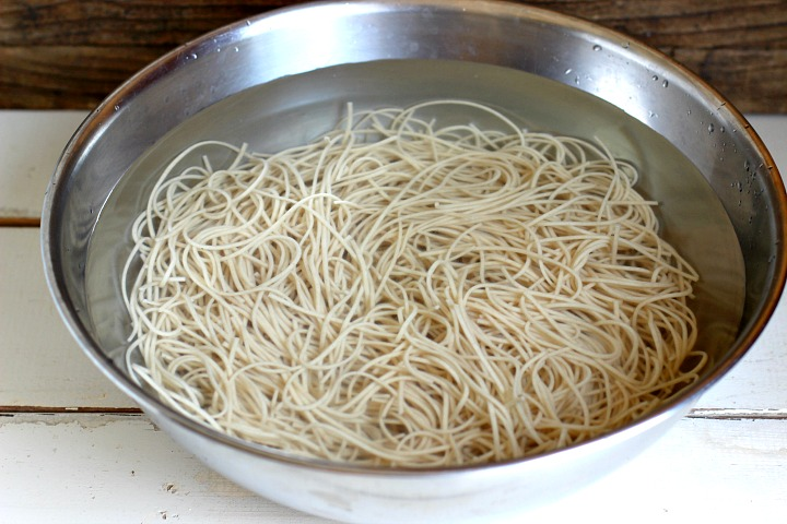 Soba Noodles being rinsed in a silver bowl of cold water