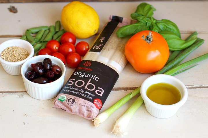 Soba noodle salad ingredients - soba noodles, cherry tomatoes, kalamata olives, olive oil, green onions, green beans, a lemon, fresh basil and sesame seeds