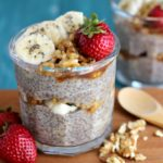 Walnut Chia Banana Pudding in a clear glass jar with walnut pieces, sliced bananas and strawberries on top