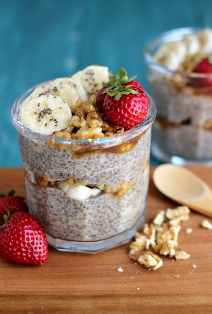 2 glass jars of chia pudding with a middle layer of banana slices and walnuts and another layer of chia pudding topped with banana slices, walnuts and strawberries.