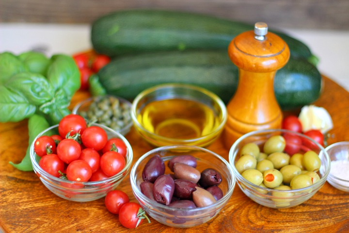 Bowls of cherry tomatoes, kalamata olives, green olives, olive oil, capers, salt, pepper grinder, 2 zucchini, garlic and fresh basil