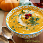 Pinterest graphic with a yellow and white bowl of butternut squash soup garnished with fresh parsley and pomegranate seeds on a wooden surface with 2 silver spoons