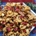 Pinterest graphic of a white plate on a royal blue background with mixed maple glazed nuts and dried cranberries