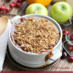 Pinterest graphic with a small white casserole dish with apple cranberry crisp baked in it and apples, oranges and cranberries in the background