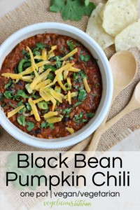 white bowl of black bean pumpkin chili topped with green onions, cilantro and shredded cheddar cheese
