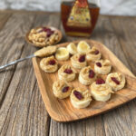 wooden plate of banana slices topped with tahini, walnut and dried cranberries