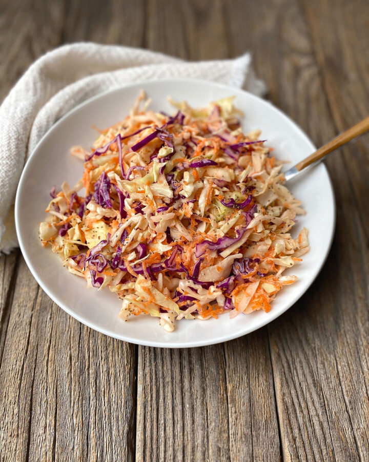 White bowl of coleslaw on a rustic surface