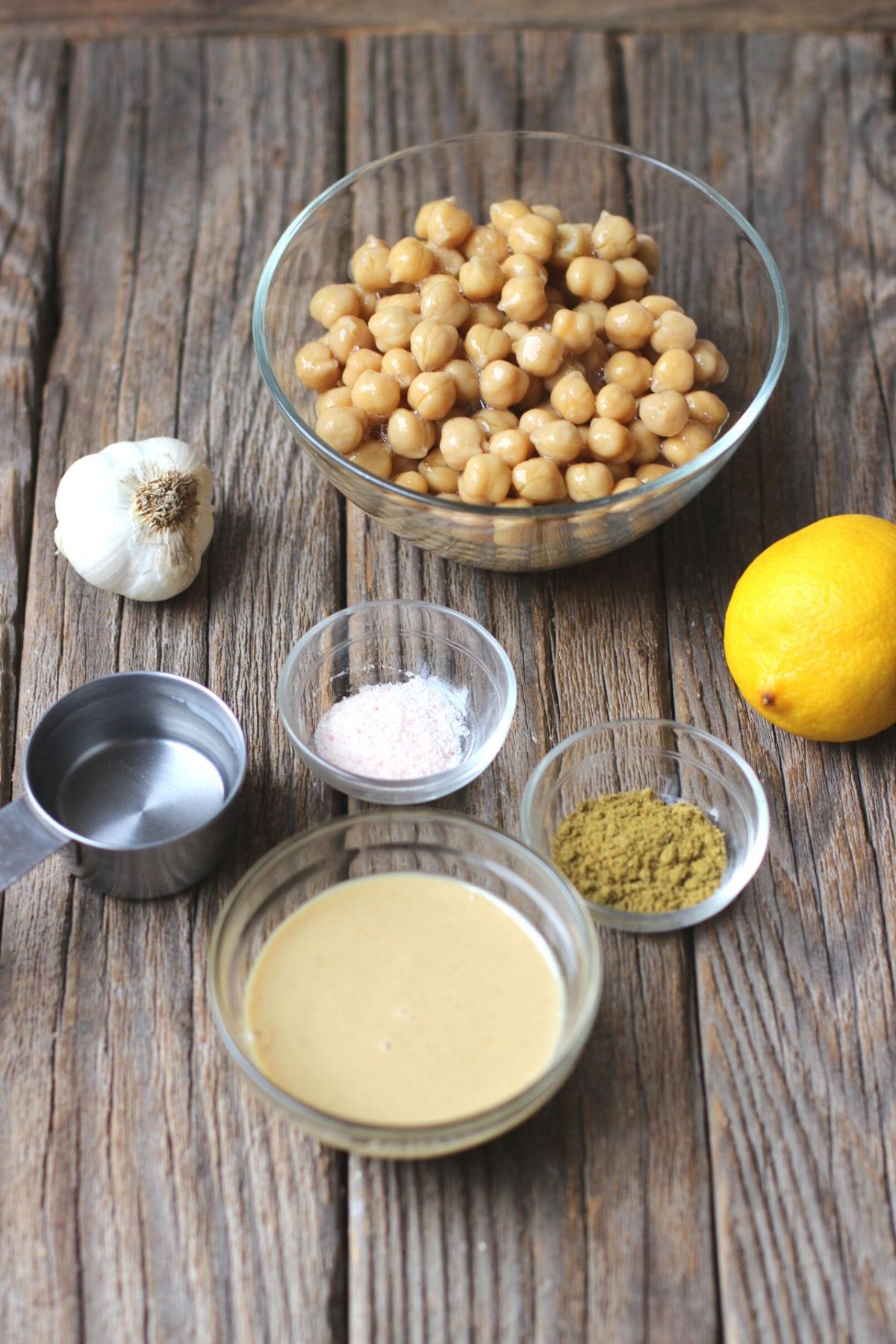 Bowl of garbanzo beans, bulb of garlic, lemon, salt, cumin, tahini and water for oil-free hummus