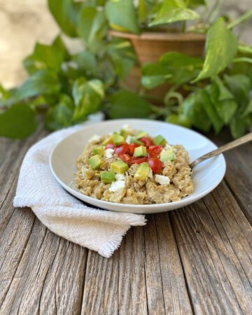 White bowl of savory oatmeal topped with feta cheese, avocado and tomatoes on a rustic surface
