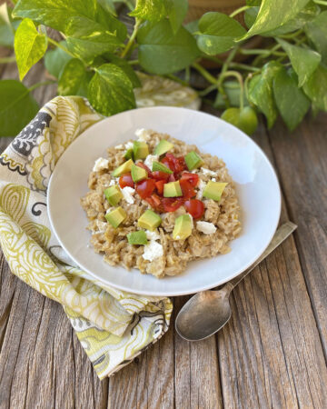 white bowl of Savory Breakfast Oatmeal topped with avocado, tomatoes and feta cheese