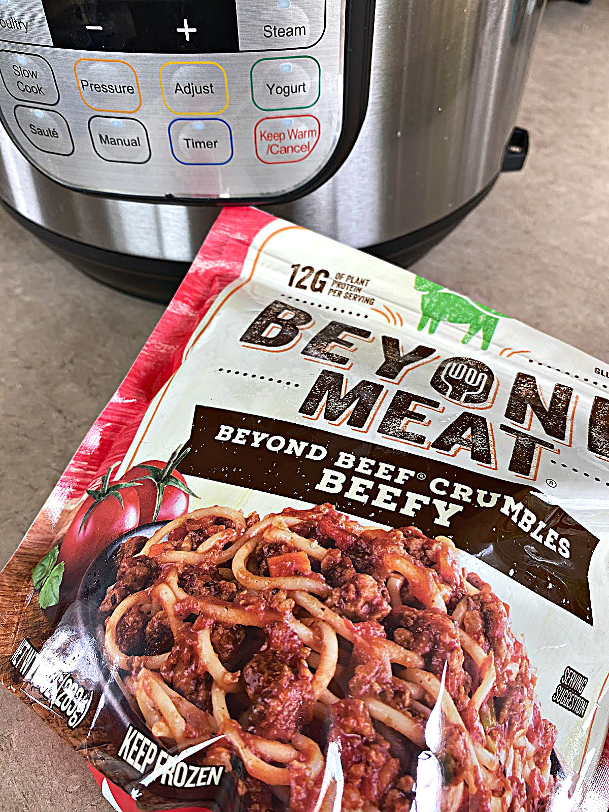 Package of frozen Beyond Meat brand Beefy crumbles with an Instant Pot in the background